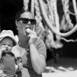Little baby girl sitting with her mother on the beach eating aan ice-cream with her hat on — Stock Photo #74942899
