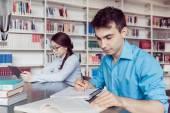 Молодые студенты, обучающиеся в библиотеке — Стоковое фото