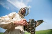Beekeeper with smoke tool. making clouds — Stock Photo