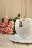 Galletas españolas para la grasa en una taza con un ramo de rosas — Foto de Stock