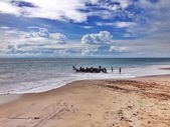 Fishermen in boat on shore of ocean — Stock Photo