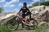 Sportsman in sportswear on a mountain bike rides on the stones in the extreme style of downhill — Stock Photo