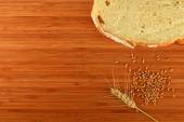 Cutting board with wheat ear, grains and slice of bread — Stock Photo