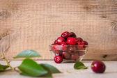 Красные вишни в стеклянной пластины на столе с зелеными листьями — Стоковое фото