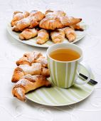 Croissants with cup of tea. — Stock Photo