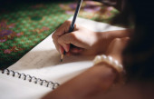 Girl's hand writing in notebook — Stock Photo