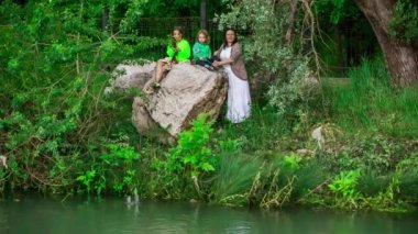 Mother And Two Children Throwing Stones Into Pond — Stock Video