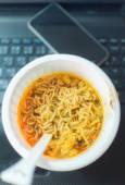 Instant noodles on black laptop — Stock Photo