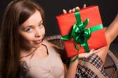 Sensual sexy attractive girl sits on a chair with gift in her hands — Stock Photo