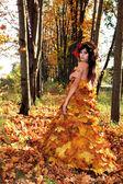 Autumn. Girl in dress of leaves, golden autumn. — Stock Photo