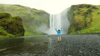 Successful Young Tourist Standing in Front of Waterfall. Skogafoss — Stock Video