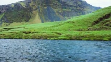 Blue River with Green Grass and Jagged Mountain Peak. — Stock Video
