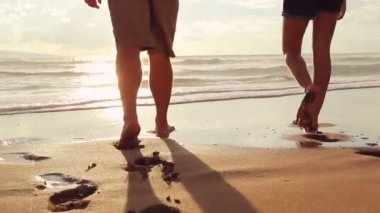 Красивая молодая пара, ходить на пляж, взявшись за руки на закате — Стоковое видео