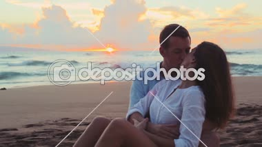 Красивая молодая пара сидя вместе целоваться на пляже закат — Стоковое видео