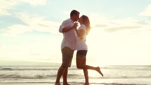 Pareja apasionada besos enamorados al atardecer de playa — Vídeo de stock