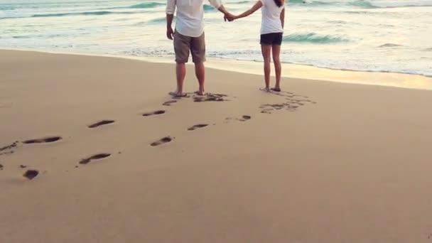 Linda joven pareja cogidos de la mano increíble puesta de sol en Playa Luna de miel en Hawaii — Vídeo de stock