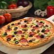 Delicious full supreme deluxe pizza baked fresh out of the oven next to ingredients — Stock Photo #77490036