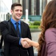 Handshake between two business people attractive smiling downtown buildings city — Stock Photo #78844100