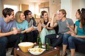 Group crowd of people friends at home in dorm playing games cards poker excited — Stock Photo