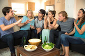 Large group of friends at a party get together house drinking beer chatting storytelling gossiping — Stock Photo