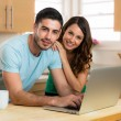 Husband and wife couple sharing a computer laptop social network laughing smiling searching for funny content with coffee — Stock Photo #79636902