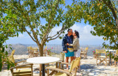 Couple of lovers kissing under trees in a restaurant with panora — Stock Photo