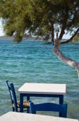 Small white table and chair overlooking the blue Aegean Sea — Stock Photo