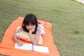 Little asian girl use pencil writing on notebook for writing book in the park — Stock Photo