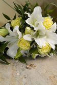 Wedding bouquet of lilies and roses, gold wedding rings — Stock Photo