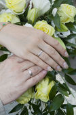 Hands of the bride and groom in wedding rings on the background of a wedding bouquet — Stock Photo