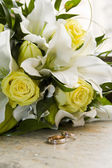 Brides bouquet of lilies and roses, gold wedding rings — Stock Photo