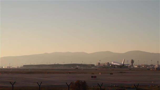 Avión aterrizando en el aeropuerto de Barcelona al atardecer — Vídeo de stock