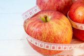 白いウッドの背景にメジャー テープで新鮮なリンゴ — ストック写真