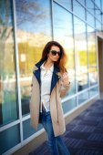 Girl in a beige coat and blue jeans — Stock Photo