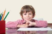 School child table looking at camera — Stock Photo