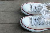 Pair of  white sneakers isolated on wooden floor — Stock Photo