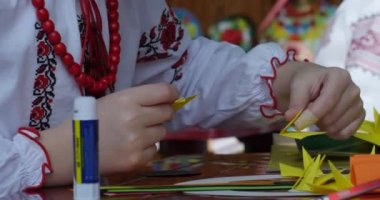 Girl In Vyshyvanka And Red Beads Makes Origami Paper Origami Tube Of Glue And Colored Paper On Table Kids Make Origami Origami Contest Making Of Kusudama — Stock Video