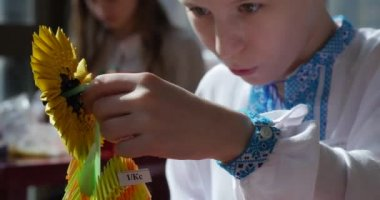 Boy In Blue-White Vyshyvanka Makes Sunflower From Paper And Puts It ToThe Paper Vase Kids Make Origami Contest Making Of Kusudama Assemble Of Modular Origami — Stock Video