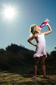A girl standing in the desert sand under the hot sun drinking wa — Stock Photo