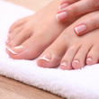Closeup photo of a beautiful female feet with red pedicure isolated on white — Stock Photo #83688898