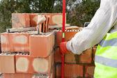 Каменщик строитель измерения с профессиональным уровнем кирпича на стенах — Стоковое фото