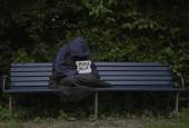 Homeless man on park bench — Stock Photo