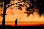 Silhouette of unidentified girl on beach with sunset light — Stock Photo