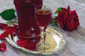 Liquor from rose petals on the wooden table — Stock Photo