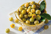 Berries yellow plums on a white wooden table — Stock Photo
