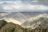 Colorful rainbow in the Nepalese mountains after the distant rain — Stock Photo