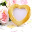 Blank photo heart wood frame with pink roses and gift box on sweet flower background — Stock Photo #78982390
