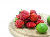 Strawberries with lime closeup over white background — Stock Photo
