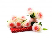 Fake roses plastic artificial flowers and red fabric — Stock Photo