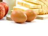 Eggs and slice bread on white background — Stock Photo